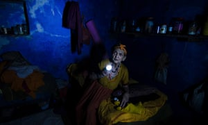 An elderly woman searches for her medicines during a power cut in the Indian city of Varanasi