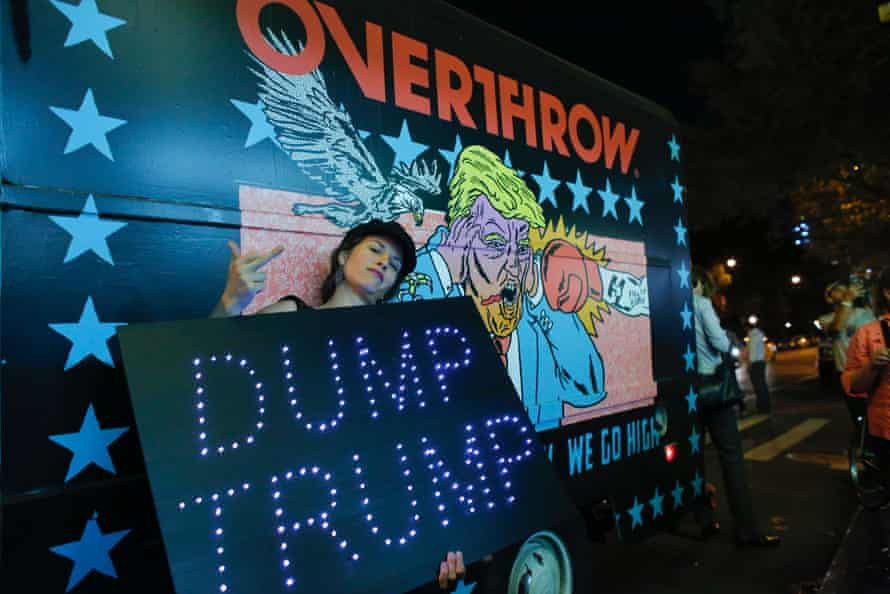 """A woman poses next to the the """"Knockout Trump Truck"""" outside the IFC Theater"""