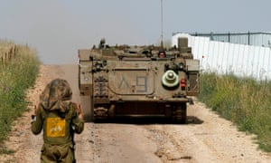 An Israeli soldier directs an armoured personal vehicle in the Golan Heights