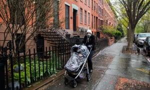 A woman wearing a protective mask carries a baby stroller during the outbreak of the coronavirus disease in the Brooklyn borough of New York City.