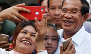 Garment workers take pictures with Cambodia's Prime Minister Hun Sen