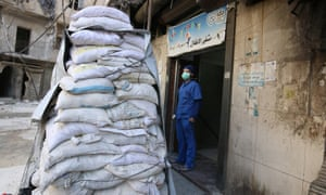 A medic stands behind sandbags outside al-Hakeem hospital, in the rebel-held area of Aleppo