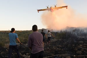 A firefighting plane drops water to extinguish a forest fire near Zadar, Croatia