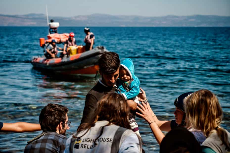 A migrant with a child is helped by rescuers as he arrives on the Greek island of Lesbos in September 2019.