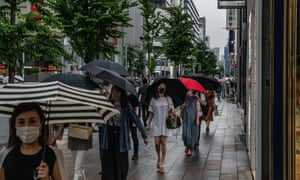 People wearing face masks as they walk along a street on Tuesday in Tokyo, where 54 new Covid-19 infections have been recorded in the last 24 hours.