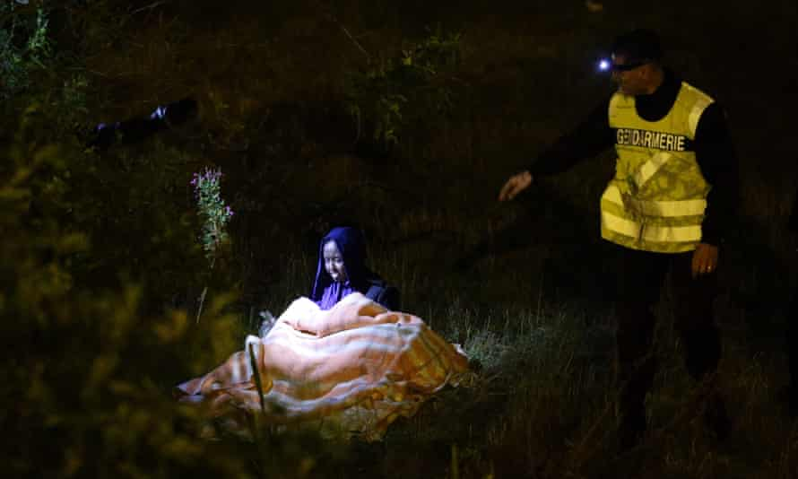 A woman and her five-year-old child (under blanket) are approached by a French police officer during a nightly patrol of the Eurotunnel perimeter fence in Calais.