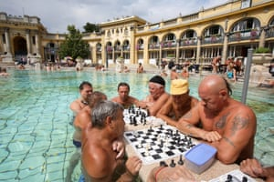Men play a game of chess while standing in the waters of the Szechenyi Furdo thermal baths