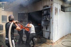 Men feed hose into building