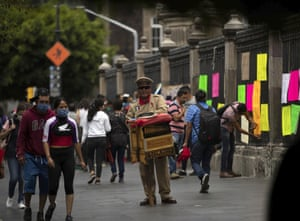 An organ grinder plays his instrument as newly graduated teachers from the state of Michoacan hang signs on the fence of the city's cathedral, during a protest demanding better salaries and jobs, in Mexico City on 13 August 2020.