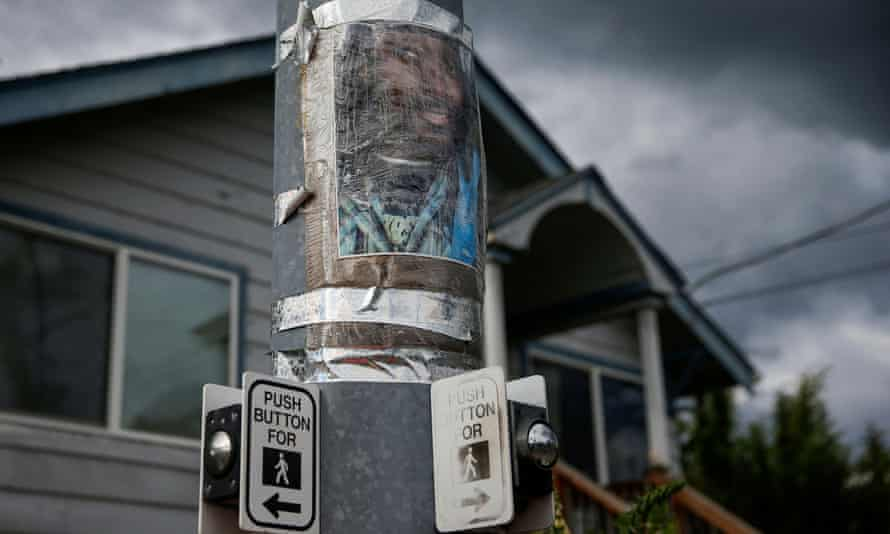 A photo of Manuel Ellis, who died in Tacoma police custody in March, is taped to a pole at a vigil site in Tacoma, Washington.