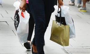 A woman carries clothing shop bags