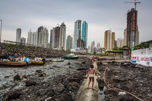 """Panama City, Panama. Longitude: -79¡50' 60.22""""Encroaching developments threaten the slum neighbourhood of Boja La Caja. A property boom has turned one of the Panamanian capital's most impoverished and notorious neighbourhoods into prime real estate and an irresistible target for developers. Buildings along the skyline have been nicknamed Ghost Towers as many of the apartments within are proving too expensive for middle-class Panamanians and the expected surge of foreign investment has yet to materialise, so at night the newly built skyscrapers are empty and dark"""