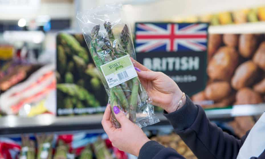 A customer holds up a pack of wonky vegetables in a Morrisons store
