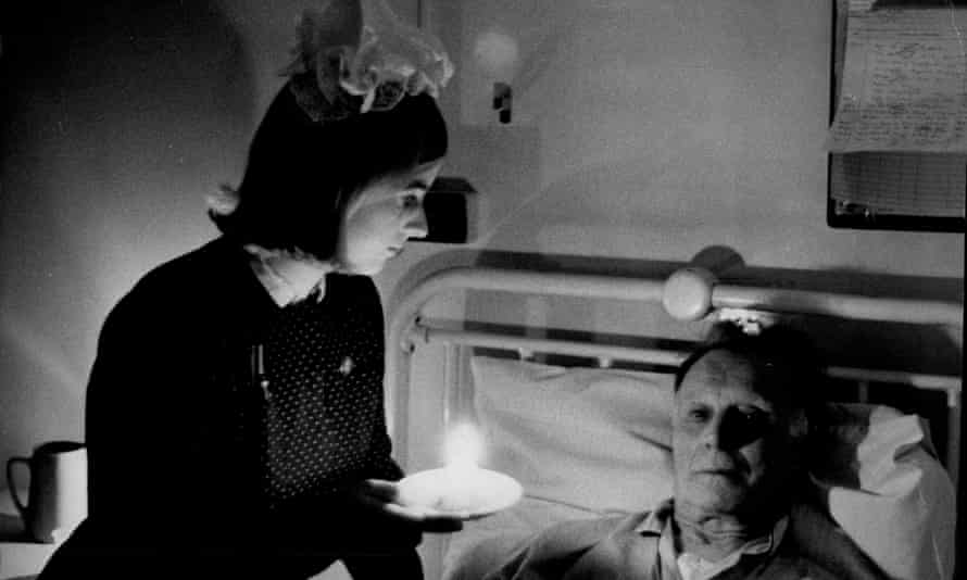 Sister Jane Davies looks at a patient by candlelight during black-out at Lambeth Hospital during the electricians work-to-rule strike.