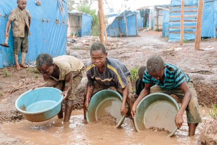 Using makeshift pans, children sluice gold ore while standing ankle deep in water