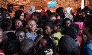 Ethiopian refugee children who fled the Tigray conflict and Sudanese helpers at a space set up by Plan International at the Hamdayet border camp.