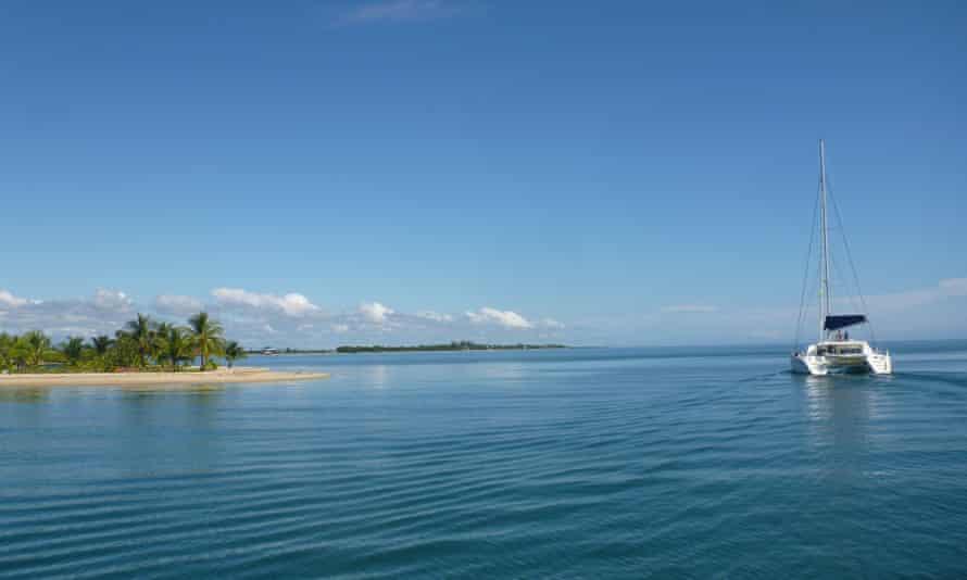 A catamaran passes a sandy caye off Belize