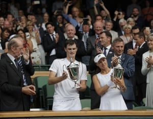 Jamie Murray and Martina Hingis examine their trophies amidst the applause of the Centre Court crowd.