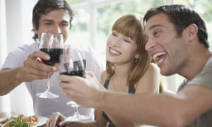 Three people toasting red wine at dinner table and smiling