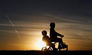 children ride a tricycle in silhouette