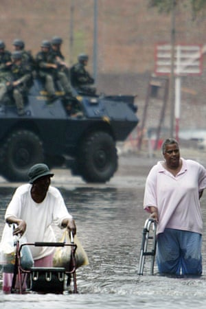 As the National Guard patrols, Louis Jones, left, and Catherine McZeal help each other walk down flooded Poydras Street in New Orleans as they go to the Superdome 1 September 2005.