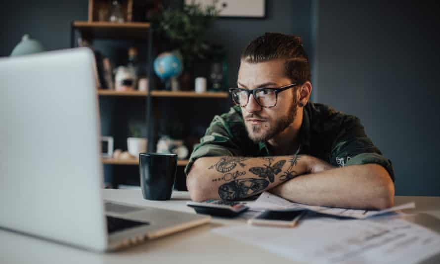 Worried student overcrowded with bills to pay is looking at laptop