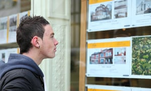 Young man viewing houses in an estate agent window