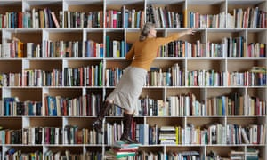 woman standing on stack of books reaching for another one