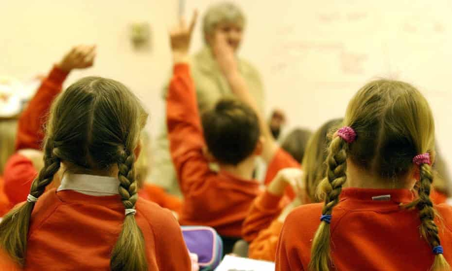 Children raise their hands in a primary school classroom.