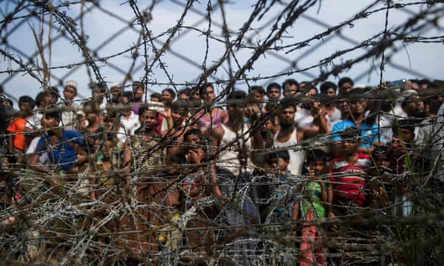 Rohingya refugees gather behind a barbed wire fence in a temporary settlement between Myanmar and Bangladesh.