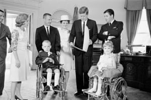 President John Kennedy looks at a gift from Bobbie Whittaker, 7, in his White House office in Washington, 20 June 1963. Bobbie and his six-year-old sister, Kerrie, right, are the new national poster children of the Muscular Dystrophy Association