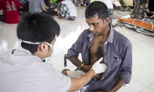 A migrant is given medical treatment at a temporary camp in Kuala Cangkoi village, North Aceh, Indonesia