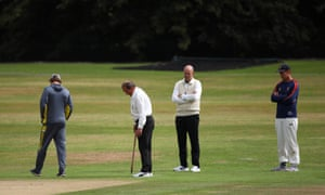 Umpires Billy Taylor and Ian Gould inspect the pitch with a stump.