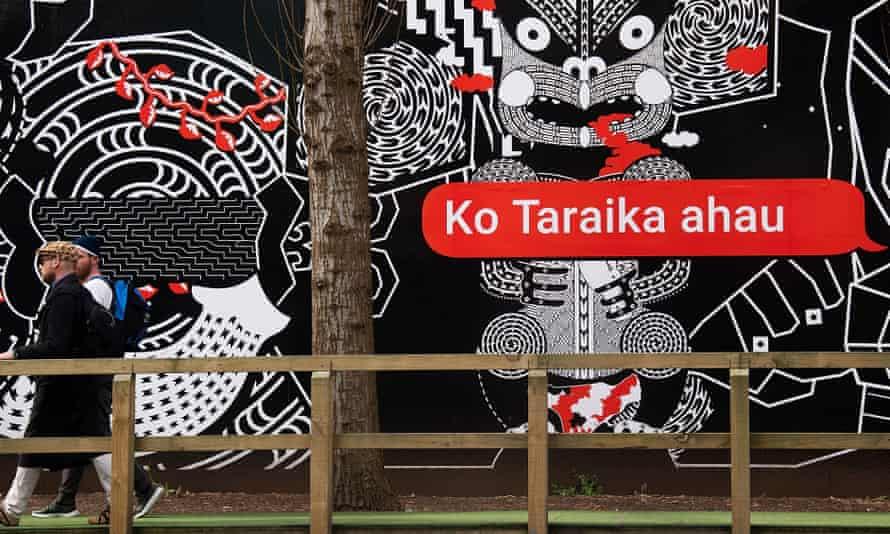 people walk past Maori language signs in Wellington on