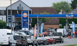 People queue for fuel at a petrol station in Barton, Cambridgeshire.