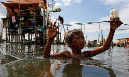 A Filipino boy holds a fishing net at a coastal village in Malabon city, east of Manila, as severe tropical storm Melor continues to heads toward the central Philippines.