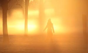 A woman walks through fog as the sun rises over over south London