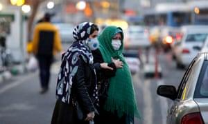 Women wearing face masks walk on a street of Tehran, Iran