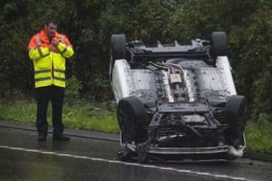 Pontypridd, WalesA man looks at a vehicle which overturned during bad weather on the A470 road after the principality of Wales had a month of rain in one day.