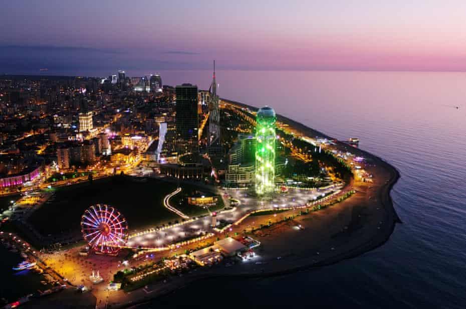 Batumi after dark, with neon lights and ferris wheel