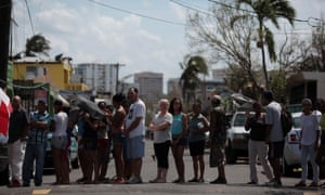 People wait in line for relief items to be distributed in San Juan Sunday.