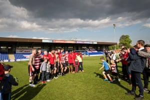 The players pose for photographs with fans after the match.