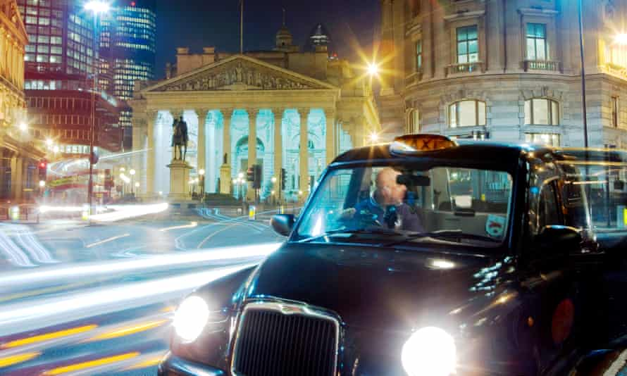 A black cab picks up a passenger in the financial district.