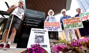 Placards are held outside the Brisbane court where the inquest into Omid Masoumali's death is being held