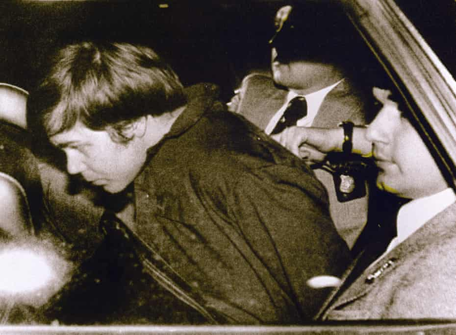 John Hinckley, left, is escorted by police on 30 March 1981 after shooting and seriously injuring Ronald Reagan.