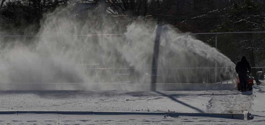 A town recreational employee clears snow from an outdoor skating rink in Burlington, Massachusetts, on Tuesday.