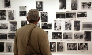"""A visitor looks at prints from the Looking In: Robert Frank's """"The Americans"""" exhibition at the Museum of Modern Art in San Francisco"""