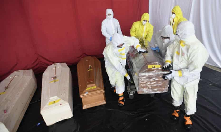 Protezione Civile workers handle the coffins of coronavirus victims at a mortuary in Ponte San Pietro, in the province of Bergamo.