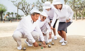 Pétanque players checking who won their game.