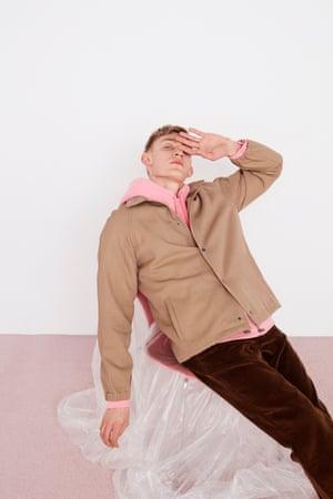 Pink zip-through hooded sweatshirt, light brown skater jacket, brown trousers